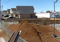 Ultra Stone Slinger placing mulch over a fence